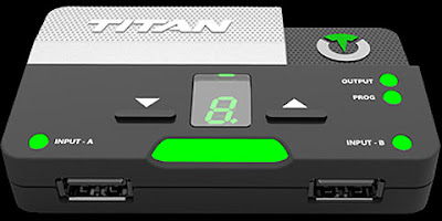 Titan Two adapter mock-up. Two USB ports on a grey and green box. Two buttons marked with up/down arrows. A small single digit seven-segment display.