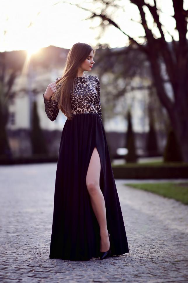 Czarna długa suknia z rozcięciem, cieliste rajstopy i szpilki