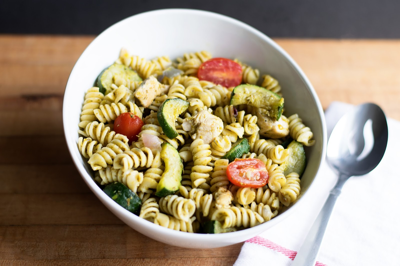 The finished Chicken Pesto Pasta Salad, in a white bowl with a serving ...