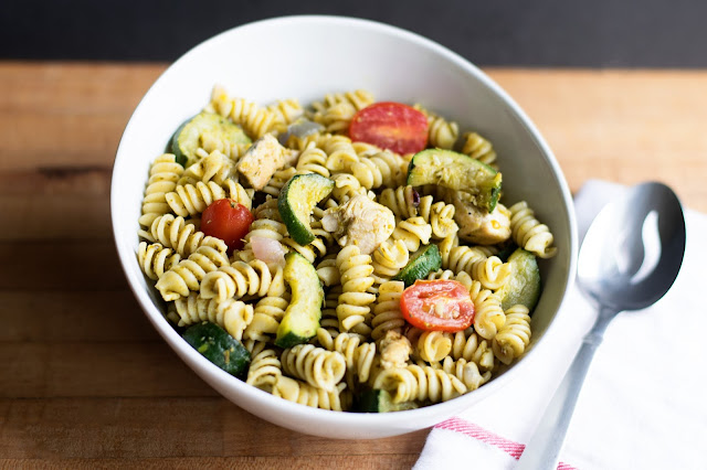 The finished Chicken Pesto Pasta Salad, in a white bowl with a serving spoon to the side.