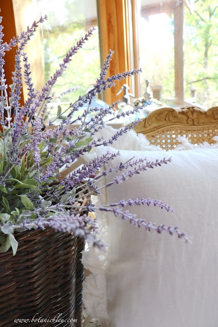 French lavender, wood carved cane-backed chairs, and ruffled linen pillows create a French Country home of your dreams
