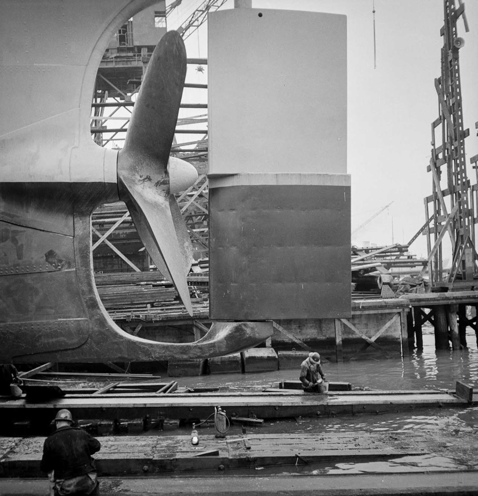 Workers grease the outboard end of a way before a launching.