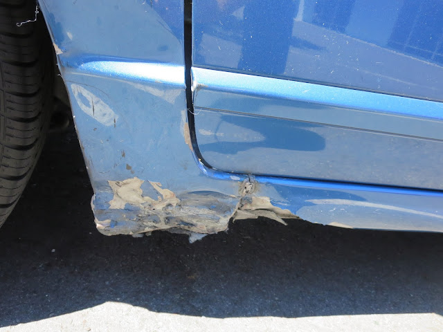 Dents in fender and side skirt before collision repairs at Almost Everything Auto Body