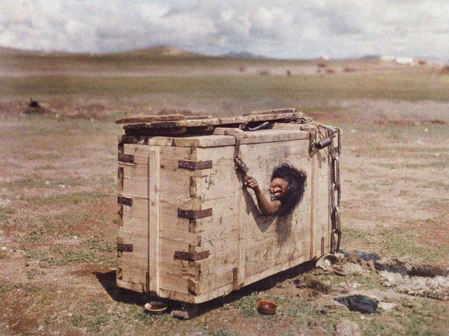 A Mongolian woman reaches out from the porthole of a crate in which she is imprisoned, c. July 1913. Note the swastika on the corner next to the lock.
