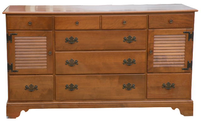 Front view of a colonial style maple dresser from the 1950s with two small doors and eight visible drawers.
