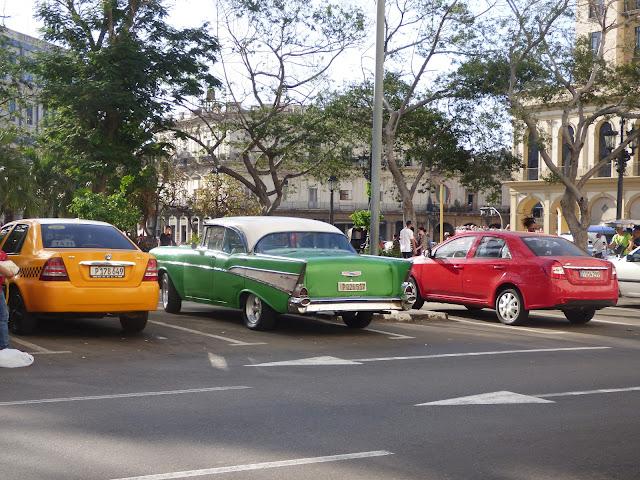 A vintage car, modern car and yellow taxi in Havana, Cuba