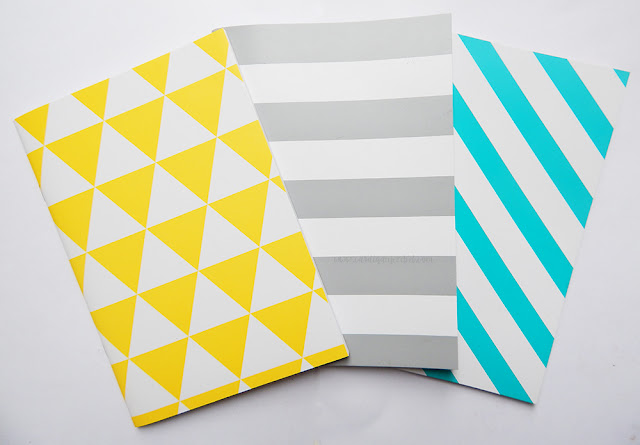 Three notebooks. Yellow and white triangles, grey and white lines, blue and white lines.