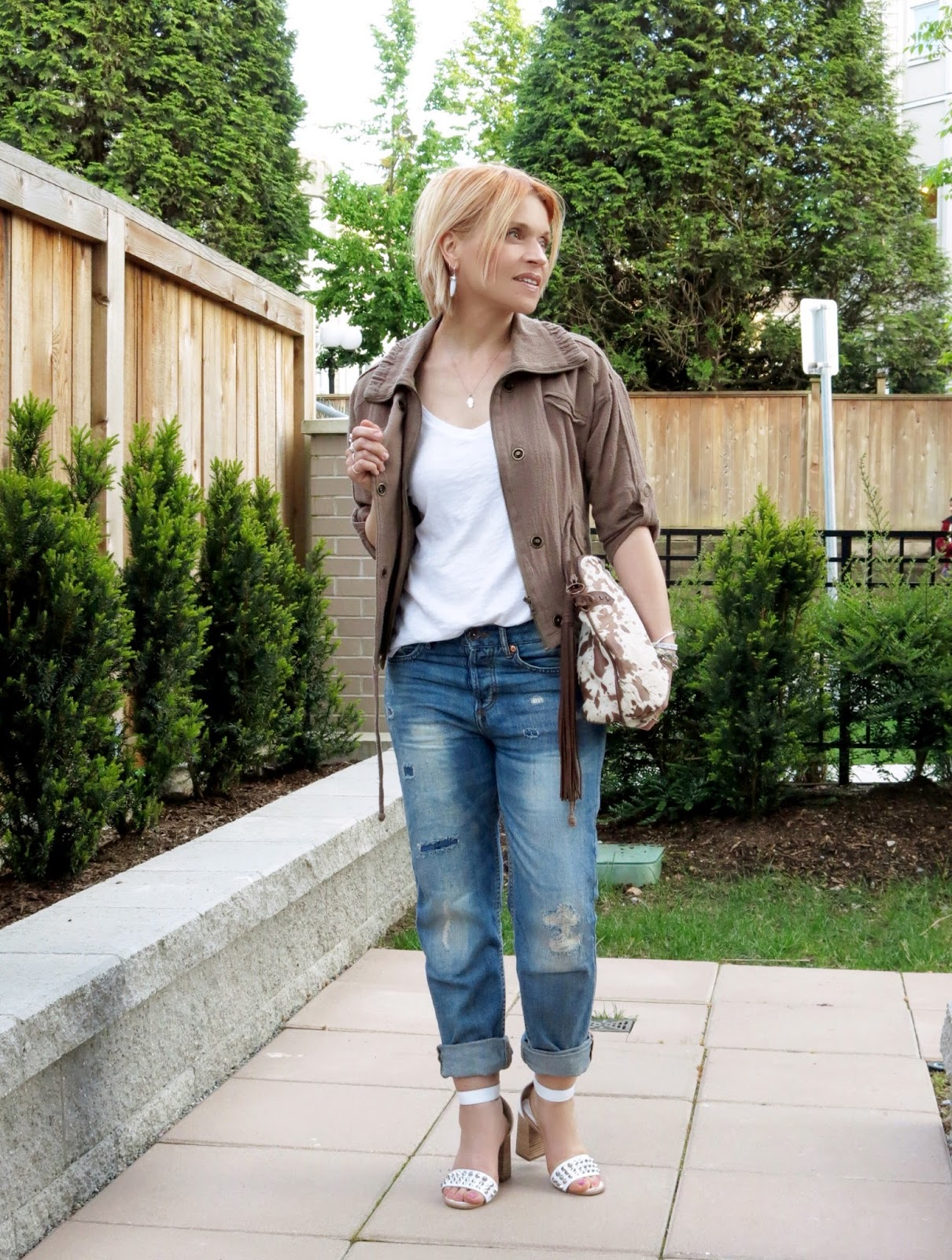 styling a slouchy tee and boyfriend jeans with a bomber jacket and ankle-strap sandals
