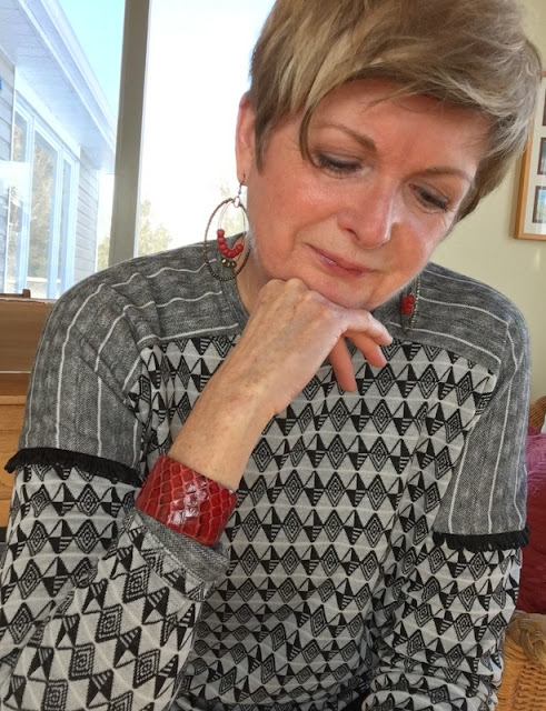 woman in a black and white figured top and a red bracelet
