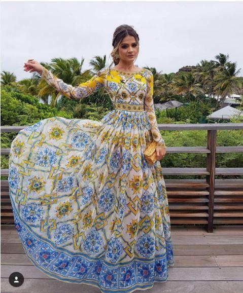 Thassia Naves posando para foto segurando a saia do vestido