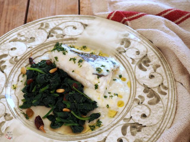 Bacalao confitado con espinacas salteadas con pasas y piñones, con crema de queso Idiazábal y aceite de perejil