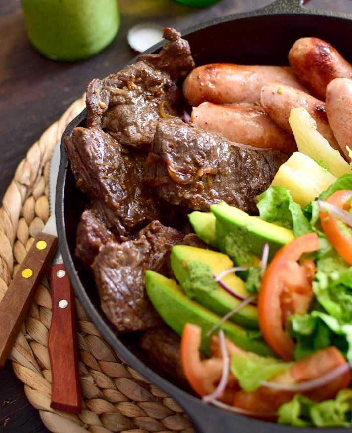 La parrilla venezolana es sinónimo de convite, celebración familiar y con amigos. Es una comida abundante. Carne y chorizos, ensalada criolla verde con aguacate, y yuca, hecha y servida en una sartén de hierro