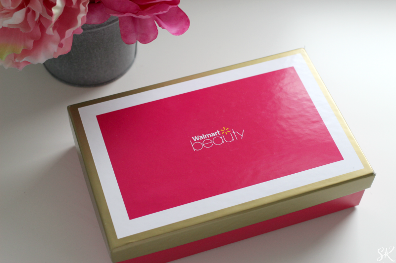 a pink Walmart beauty box on a white table with pink flowers