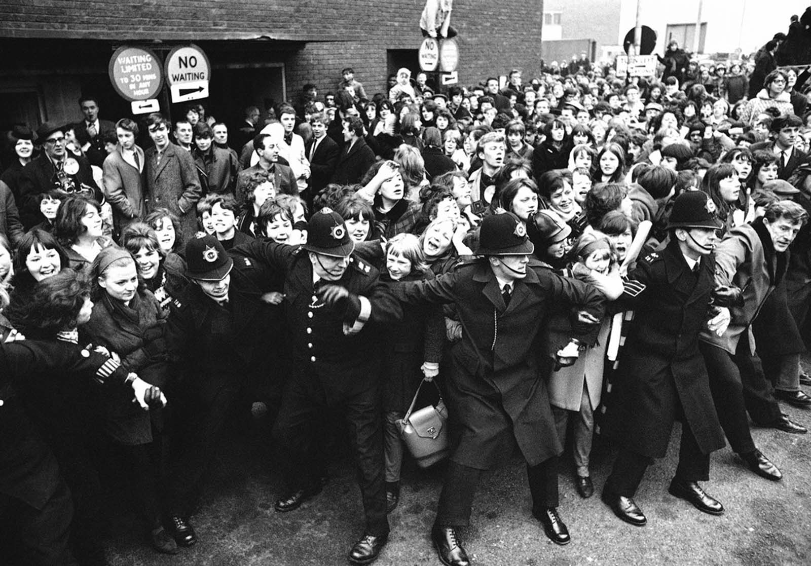 Policemen good-humoredly control screaming Beatles fans as the Liverpool pop group were welcomed by a group of more than 5,000 on their arrival at London Airport, on February 22, 1964, on their return from America.