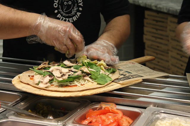 Pizza piled high with fresh ingredients at Olive Theory Pizzeria