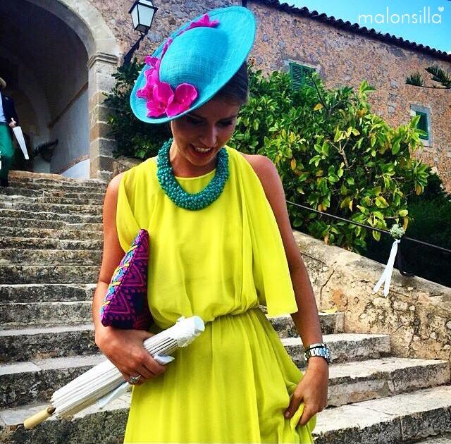 Invitada con vestido amarillo vaporoso, tocado turquesa y complementos fucsia