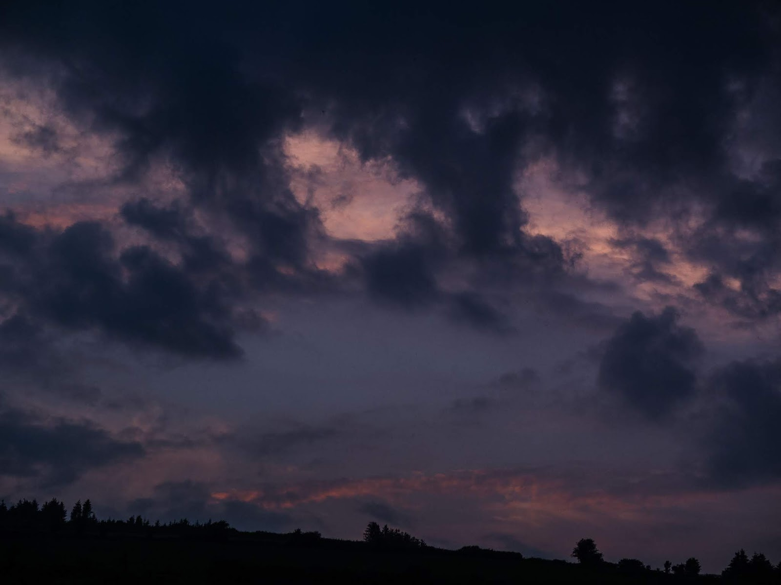 Dark clouds hovering over a sunset on a mountain side in the Boggeragh Mountains in Co.Cork.