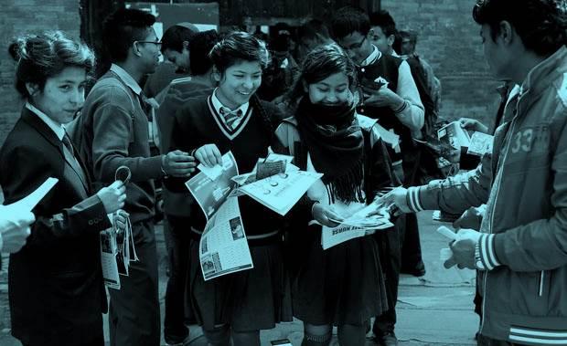 Escolares ojeando flyers