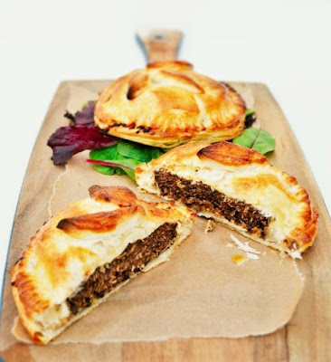 Layered Veggie Burger Pies in puff pastry, cut open on a board