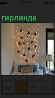 На стене висит причудливая гирлянда из лампочек и разных открыток. Рядом торшер и окно