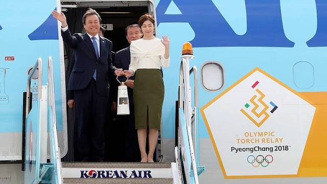 South Korean Minister of Culture, Sports and Tourism Do Jong-whan, left, and former South Korean Olympic figure skating champion Yuna Kim, hold the Olympic flame upon arrival at Incheon International Airport in Incheon, South Korea, Nov 1, 2017. (AP Photo/Lee Jin-man)