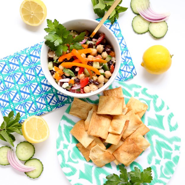 Greek Garbanzo Bean Salsa Dip filled with fresh mint and parsley, black beans, tomatoes, cucumbers, feta cheese, and a lemon vinaigrette. The perfect salad for a pot luck, BBQ, or picnic! Make ahead salad.