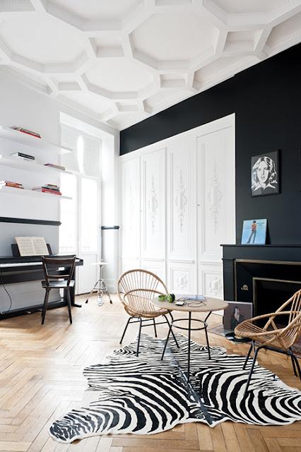 tapis en peau de zèbre, sièges en rotin, murs noirs et plafond aux moulures modernes et géoétriques