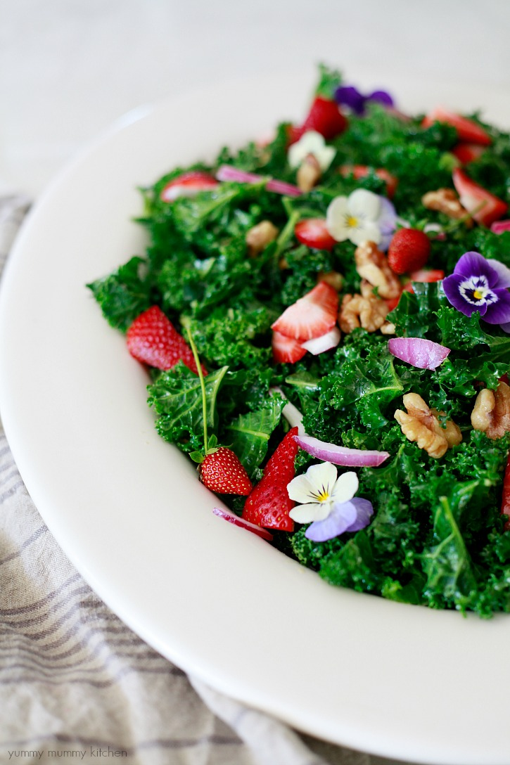 Closeup of a delicious raw vegan kale salad massaged with an easy dressing and topped with strawberries, walnuts, onions, and edible flowers.