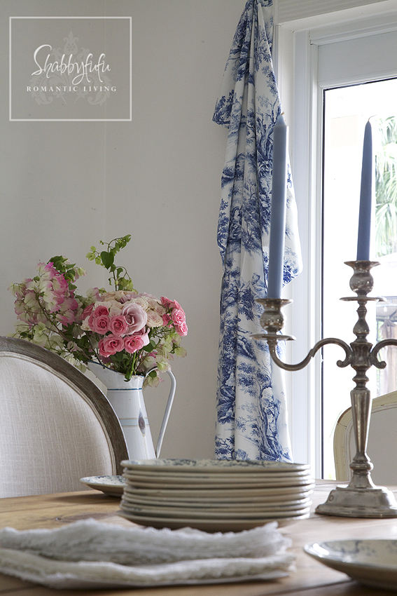 Decorating with toile - toile curtains, a bright pink floral bouquet and elegant blue candlesticks