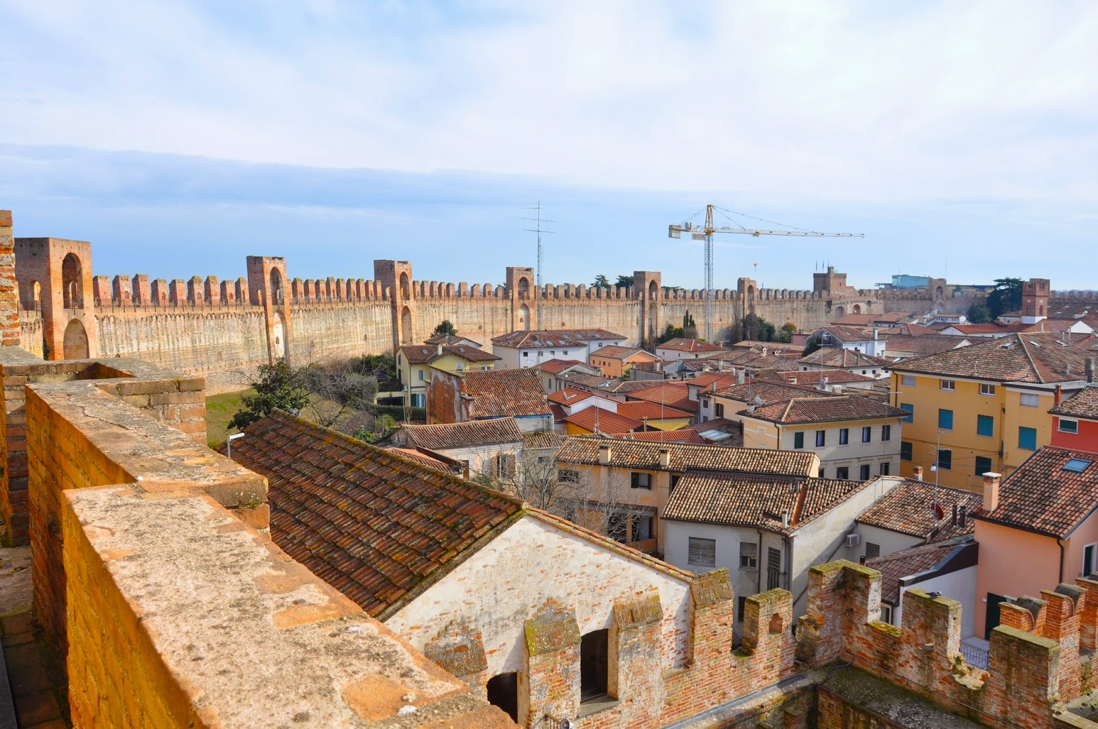 The medieval wall of the town of Cittadella in Italy with a crane in the distance