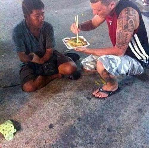 du khách người nước ngoài không ngại đút thức ăn cho người ăn xin
