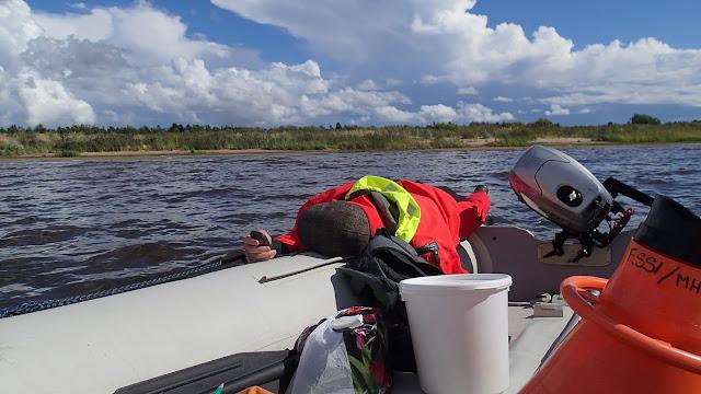 Pelastautumispukuinen henkilö retkottaa kumiveneen ponttoonilla
