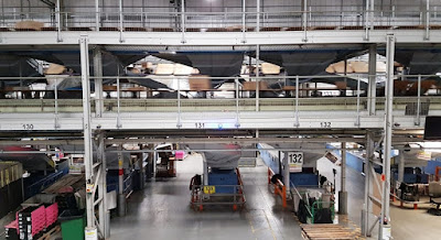 Parcels whizzing past on a conveyor high above inward and outward parcel sorting