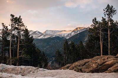 Precioso paisaje de bosque, piedras y montañas con nieve