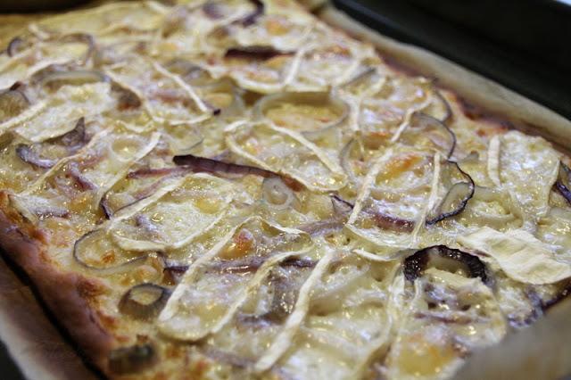 Fertig gebackener Flammkuchen mit Ziegencamembert und roten Zwiebeln bevor er mit Honig beträufelt wurde.