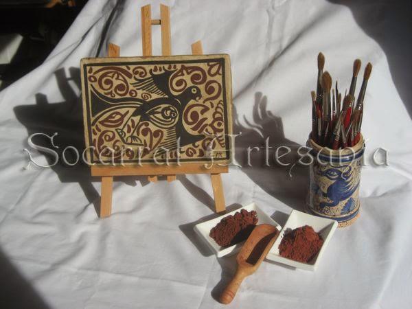 Socarrat en caballete junto a pinceles y óxidos para su realización artesanal