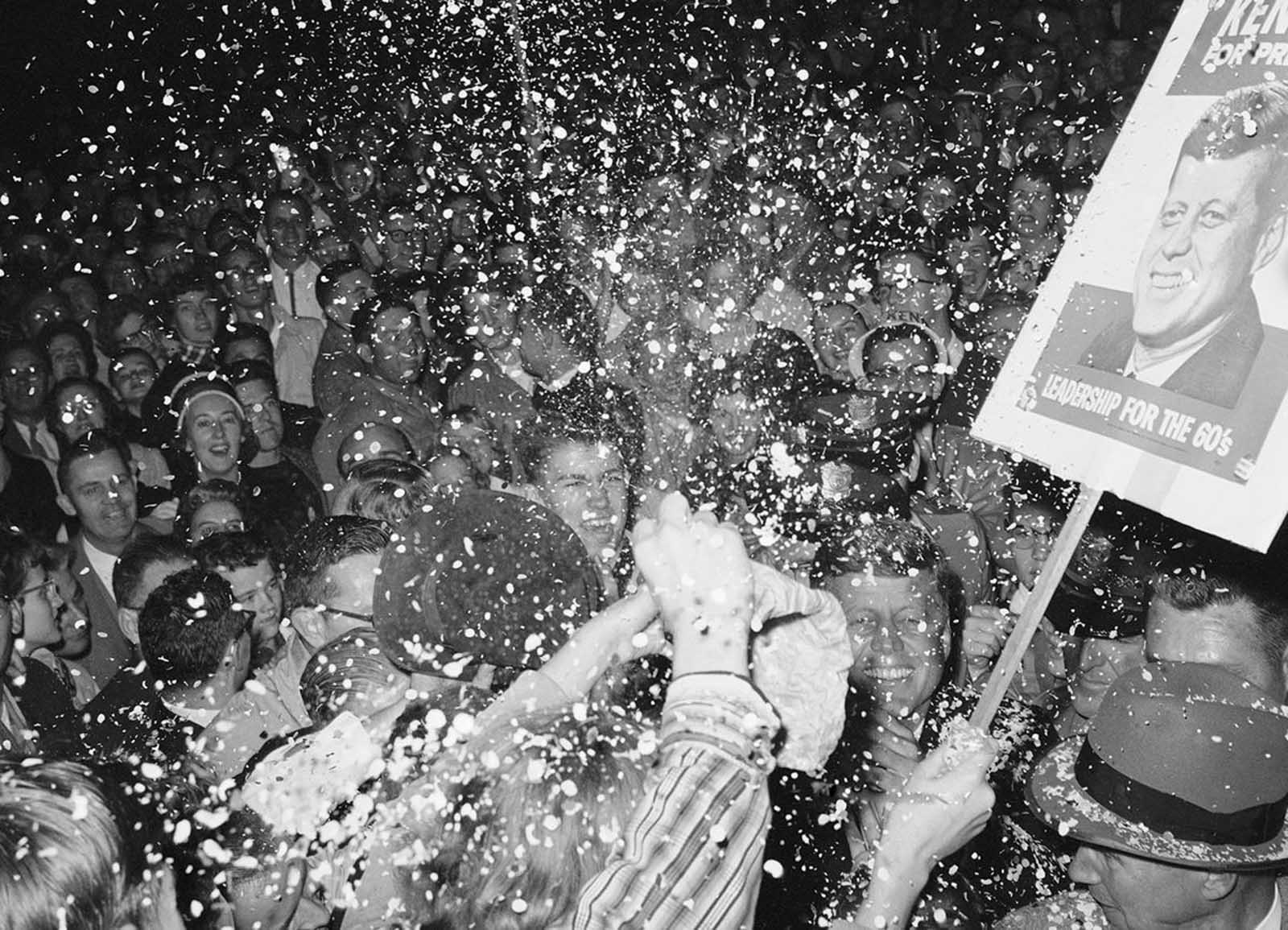 Senator John F. Kennedy, (lower right), grins happily as backers cheer the Democratic presidential candidate in Minneapolis, on October 1st. Kennedy was leaving his hotel for a rally and was surrounded by a large crowd of partisans on October 2, 1960. They waved banner threw confetti and yelled heartily. Between 18,000 and 20,000 attended the rally and thousands more were turned away.