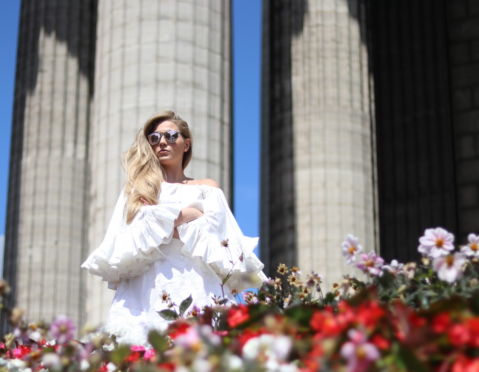 Blonde Girl, Katie Heath wearing all white in front of Pillars, Paris, France