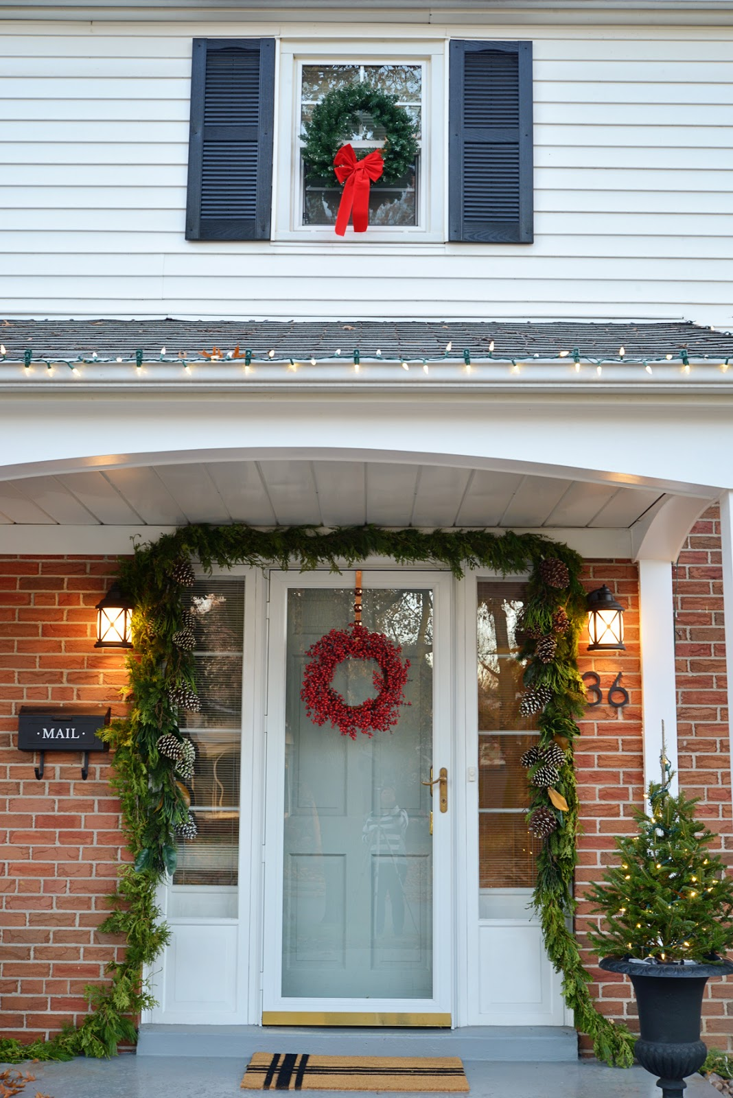 red brick classic house, christmas garland around door, coastal outdoor lighting, mailbox with decal, trees in urn