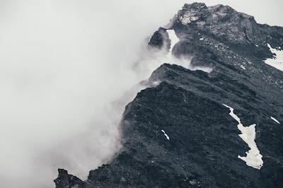 Brutales montañas negras con nubes al lado