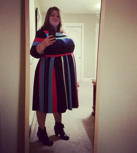 image of me in a full-lenth mirror, wearing a colorful striped dress and ankle boots