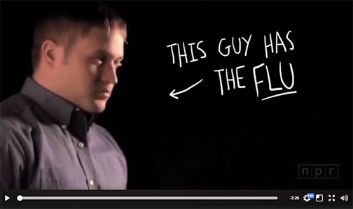 snapshot from NPR video.  Man standing off to the side.  Text: This Guy Has the Flu!