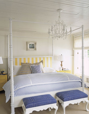 This new England style bedroom, from House Beautiful, showcases a white  chandelier over a white four poster bed.