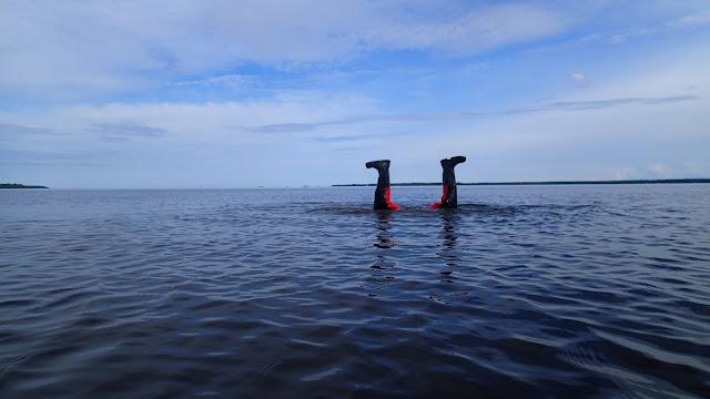 Kartoittaja seisoo vedessä päällään, vain jalat ilmassa vedenpinnan yläpuolella.