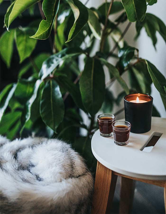 Mesinha de café simples decorada com uma linda vela em castiçal preto.