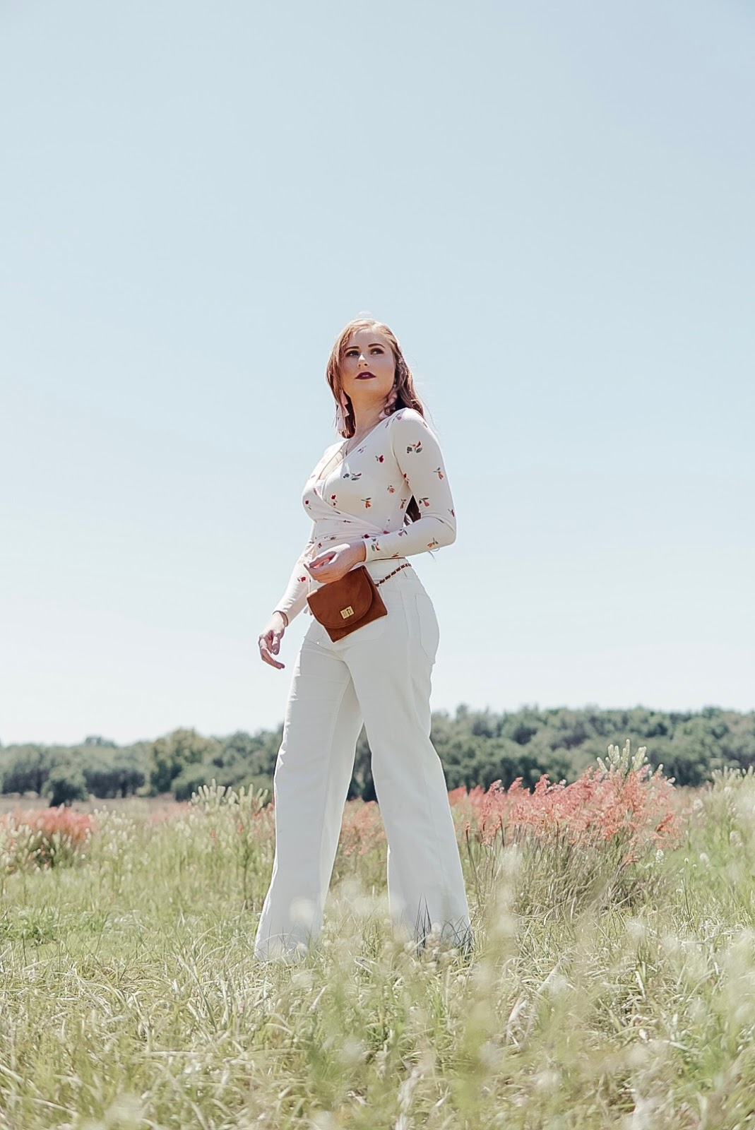 tampa blogger amanda burrows from the blog affordable by amanda is wearing a floral wrap top and white corduroy pants in the wildflower fields in dade city, florida.