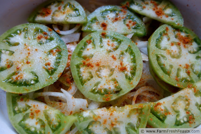 sliced green tomatoes and white onions sprinkled with curry powder in a casserole dish