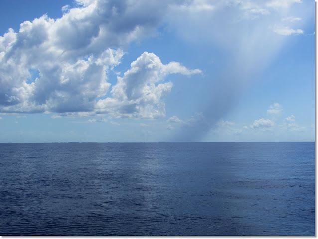 High altitude rain falls from cloud line above flat ocean horizon.