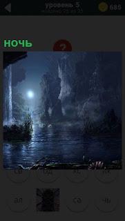 Ночь и только луна освещает озеро и горы рядом с сосульками