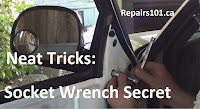 using socket wrench on side view mirror of truck